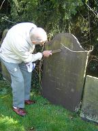 Des very painstakingly trying to make the words on Joel's headstone more legible